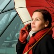 Beautiful brunette with red umbrella talking on the phone — Stock Photo #4804070