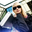 Beautiful young woman with silver case near the modern office bu - Stock Photo