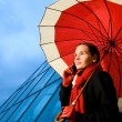 Beautiful brunette with red umbrella talking on the phone — Stock Photo #4804186