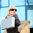 Royalty-Free Stock Photo: Beautiful young woman with silver case near the modern office bu