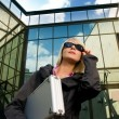 Beautiful young woman with silver case near the modern office bu — Stock Photo
