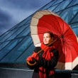 Beautiful young woman with red umbrella on rainy day — ストック写真