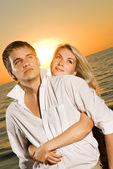 Young couple in love near the ocean at sunset — Stock Photo