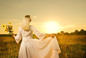 Beautiful woman with sunflowers in the field at sunset — Stock Photo