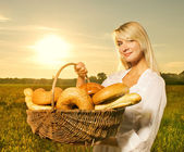 Beautiful young woman with a basket full of fresh baked bread — Stockfoto