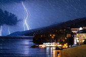 Small city near the ocean at stormy night (with realistic rain e — Stock Photo