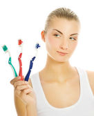 Beautiful young woman with three different types of toothbrushes — Stock Photo