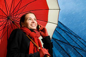 Beautiful brunette with red umbrella talking on the phone — Stockfoto