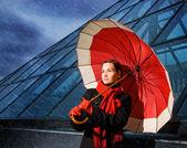 Piękna młoda kobieta z czerwony parasol na deszczowy dzień — Zdjęcie stockowe
