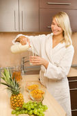 Beautiful young woman in a white dressing-gown making breakfast — Stock Photo