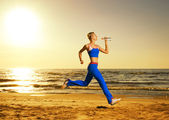 Beautiful young woman running on a beach at sunset (real shot, b — Foto Stock