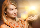 Beautiful woman holding magic lights in her hands — Stock Photo