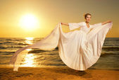 Beautiful young woman dancing on a beach at sunset — Stock Photo