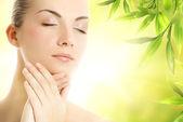 Beautiful young woman applying organic cosmetics to her skin — Stock Photo