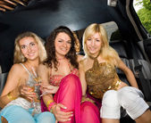 Three beautiful women in a limousine — Stock Photo