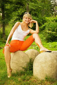 Beautiful young woman sitting on a stone in a forest — Stock Photo