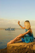 Beautiful young woman welcomes boat with tourists — Stock Photo