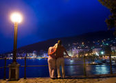 Couple standing near the sea and looking at night city panoram — Stock Photo