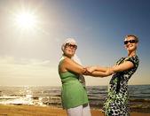 Two beautiful women sitting on the beach — Stock Photo