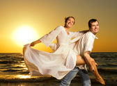 Young couple having fun near the ocean at sunset — Stock Photo