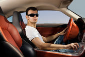 Handsome young man driving modern sport car — Stock Photo