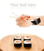 Hand holding sushi maki with wooden chopsticks — Stock Photo