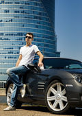 Handsome man standing near the modern sport car — Stock Photo