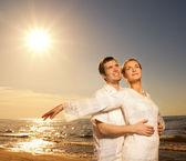 Krásný mladý pár relaxaci u moře při západu slunce — Stock fotografie