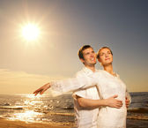 Vackert ungt par avkopplande nära havet i solnedgången — Stockfoto