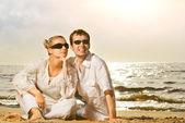 Unga vackra par avkopplande på stranden — Stockfoto