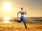 Beautiful young woman running on a beach at sunset (real shot, b — Stock Photo