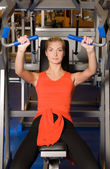 Beautiful woman works out in a gym — Stockfoto