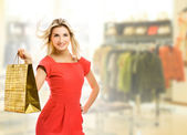 Beautiful young woman with a bag in a shop — Stock Photo