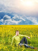 Relaxed young man sitting in a flower field — Stock Photo