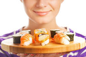Happy woman holding bamboo plate with fresh sushi set on it (Sha — Stock Photo