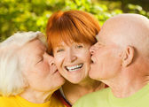 Senior parents kissing their daughter outdoors — Stock Photo