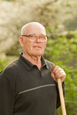 Elderly man relaxing after work in garden — Stock Photo