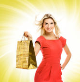 Beautiful young woman with a bag over abstract yellow background — Stock Photo