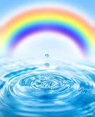 Raindrops falling into water and colorful rainbow behind it — Stockfoto