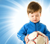 Handsome boy with soccer ball over abstract blue background — Zdjęcie stockowe