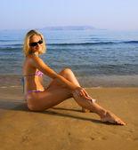 Mooie jonge vrouw scheren haar benen op een strand — Stockfoto