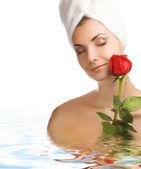 Mooie jonge vrouw met een roos in water — Stockfoto