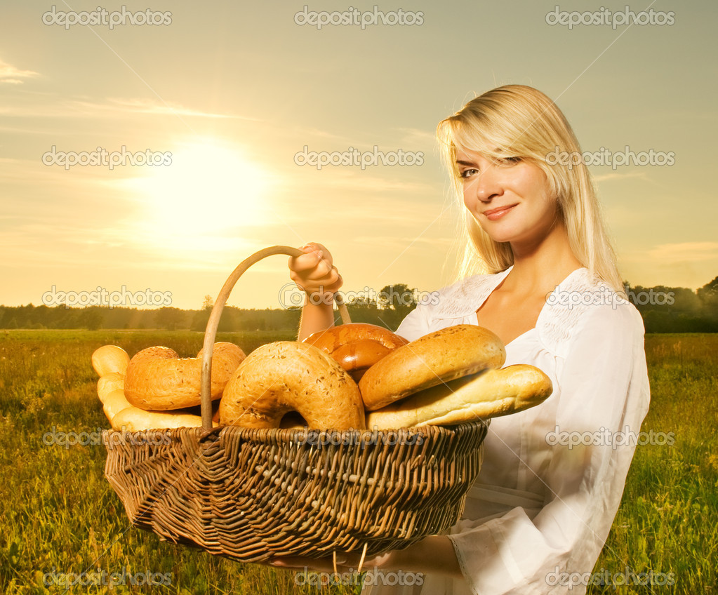 Beautiful young woman with a basket full of fresh baked bread — Stock Photo #4800471