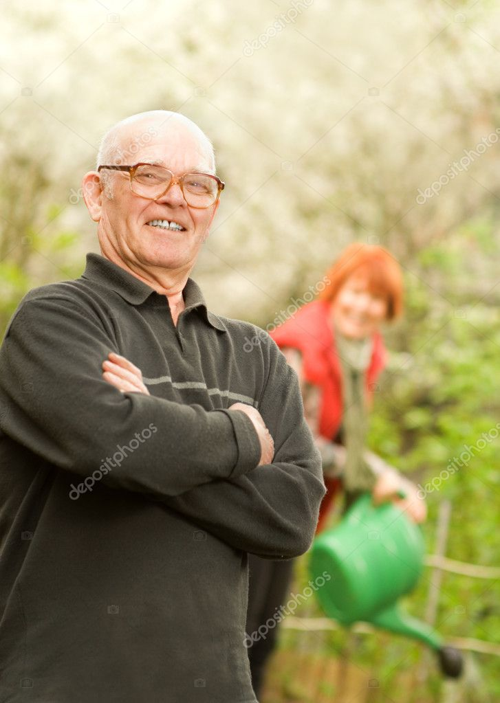Happy senior gardener and woman watering plants on a background — Stock Photo #4804152