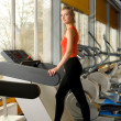Beautiful young woman running on a treadmill in a gym alone — Stock Photo