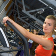 Beautiful young woman doing exercise in a gym while listening to — Stock Photo