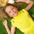 Happy young girl lying on a green grass — Stock Photo