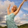 Pretty young woman over blue cloudy sky — Stock Photo