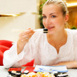Beautiful girl eating sushi in a restaurant — Stock Photo
