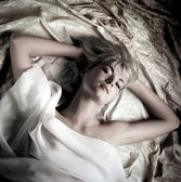 Monochrome portrait of a lovely beautiful girl lying in a bed — Stock Photo